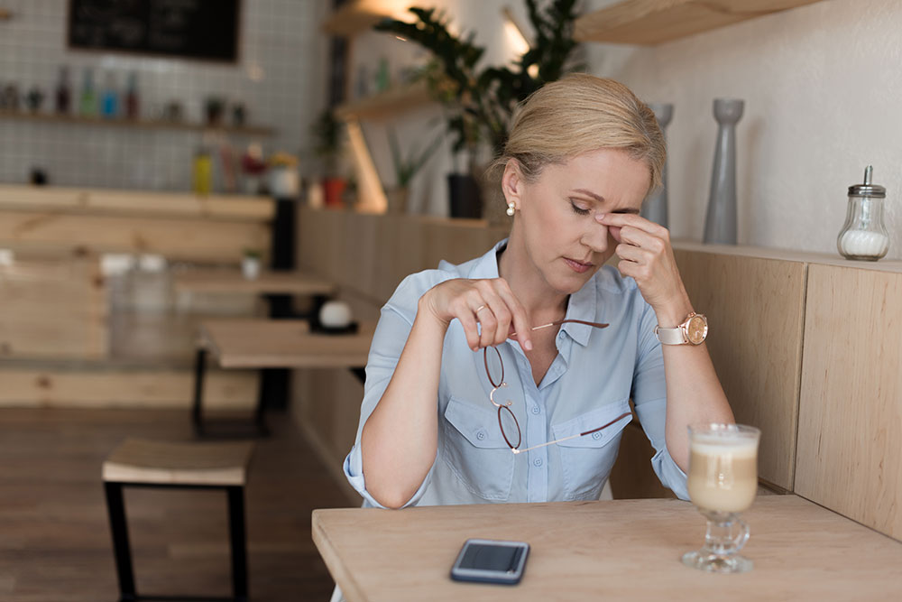woman at cafe pinching top of nose and closing her eyes